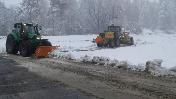 Roading contractors work to clear snow and ice on Inland Rd, Kaikoura.
