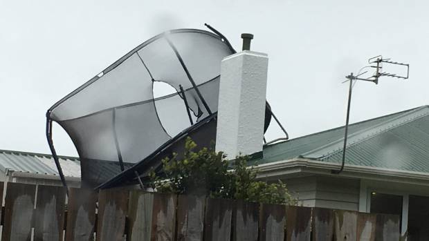 Strong winds blow a trampoline onto the roof of a house in Patea