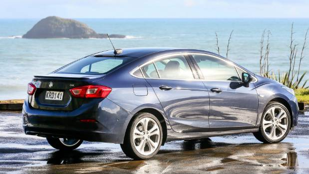 The new Holden Astra sedan parked overlooking Muriwai Beach during its first New Zealand drive.