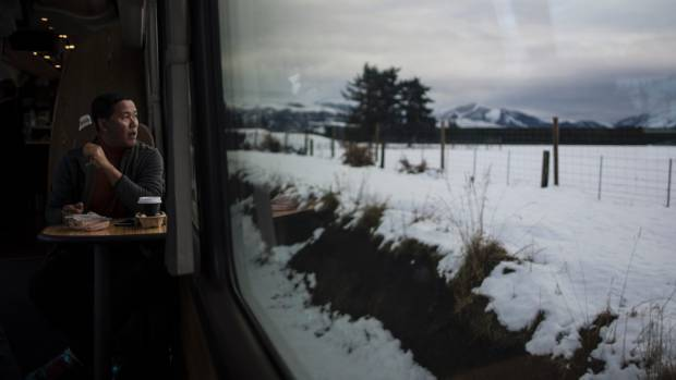Thai tourist Sompong Boonnon enjoys the sight of snow through a train window in the South Island last week.