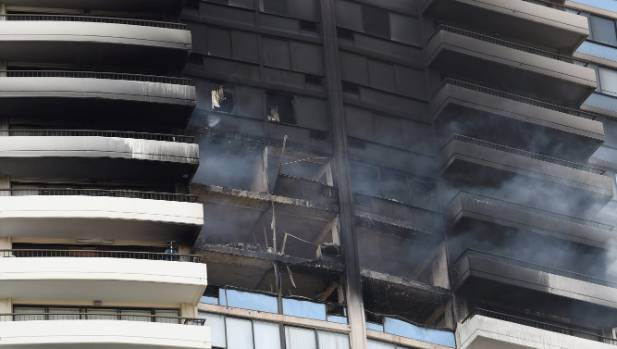 Smoke billows from the upper floors of the high-rise complex