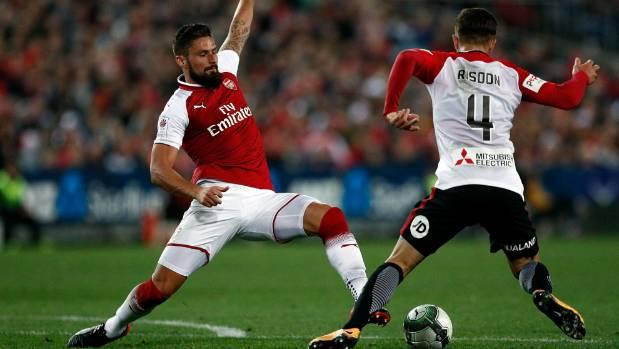 Arsenal striker Olivier Giroud challenges the Wanderers' Josh Risdon.