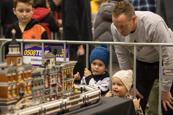 Amos Banbury and his children, Harry Banbury, 4, and Mila Banbury, 2, check out a moving train in a city exhibit.