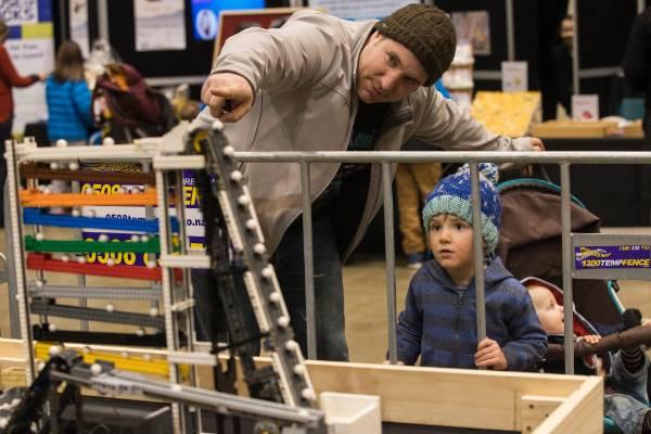 Cain Donovan shows his son Cohen Donovan, 3, a moving Lego exhibit.