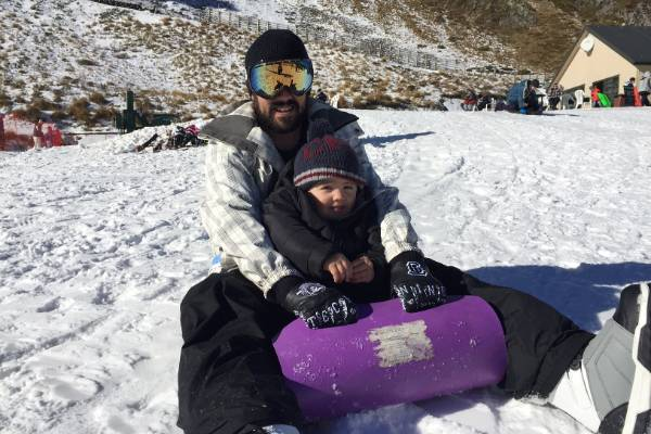 Blenheim man Sonny Puru and his two-year-old son, Tyrese, slide down a nice little slope outside the cafe at Rainbow Ski ...