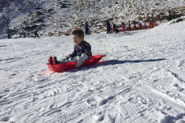 Koby Campbell, 4, picks up some speed sliding down a snow-covered slope on a sledge.