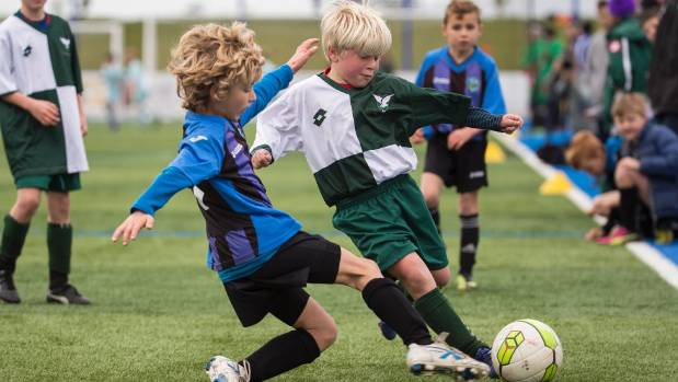 Halswell player Oliver Jones evades a defender from opposition team Selwyn in a under 9 match.