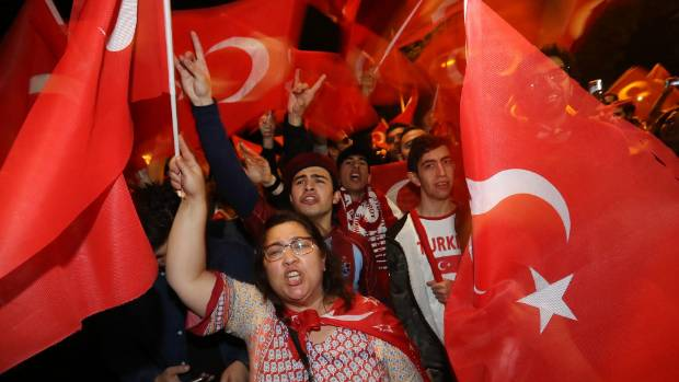 Pro-Erdogan Berlin Turks wave Turkish flags during a gathering to commemorate the first anniversary of the failed coup.