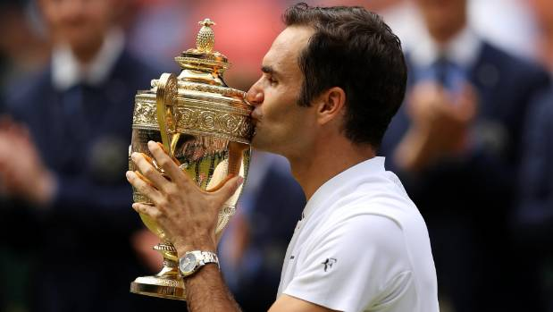 Roger Federer kisses the trophy as he celebrates an eighth Wimbledon title.