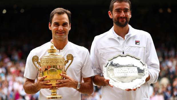 Roger Federer of Switzerland celebrates victory with the trophy alongside runner-up Marin Cilic of Croatia after the ...