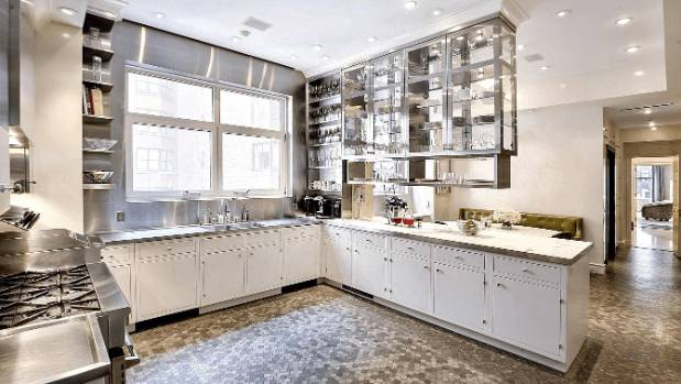 The kitchen has a hexagonal mosaic tile floor, and an upscale-utilitarian combination of stainless steel and marble surfaces.