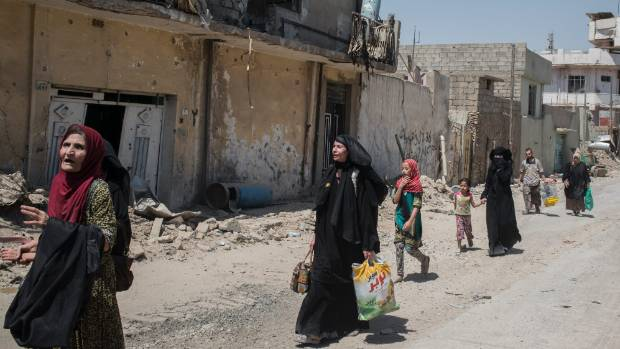 Iraqi civilians flee the Islamic State controlled Old City of west Mosul where heavy fighting continues.