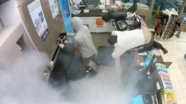 A number of offenders are seen trying to break into a secure metal cigarette dispenser during a robbery at Z Pakuranga.