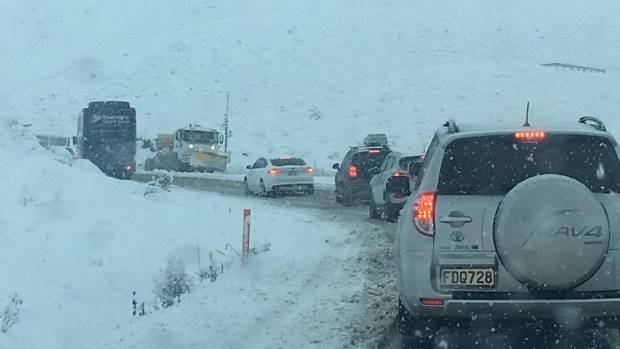 Traffic crawls through the Lindis Pass on State Highway 8 as roading contractors work to move snow off the road on Monday.