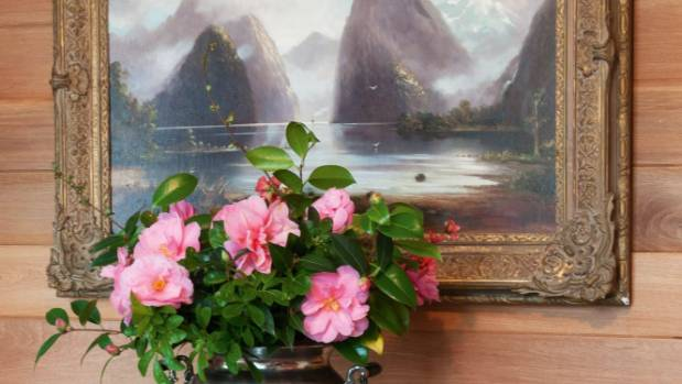 A vase of camellias sits on the dining room sideboard under an early New Zealand painting of Mitre Peak.
