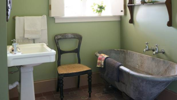 The downstairs bathroom has an original ceiling, while the floor tiles and iron bath were Trade Me finds.