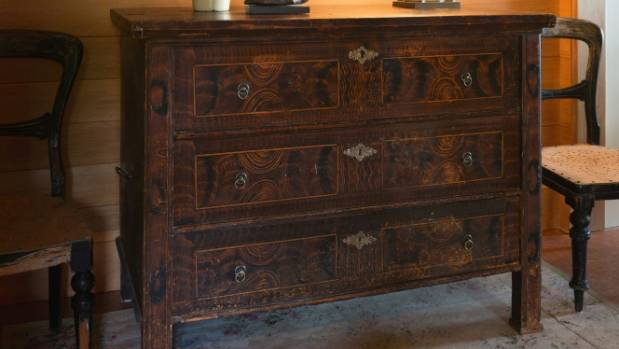 A hand-painted European cabinet sits on salvaged vintage lino.