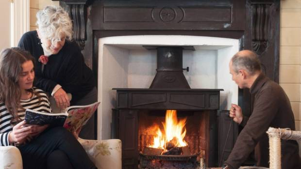 Stephen, Theresa and their daughter Olivia by the fire in the living room, with its hand-painted chequer-board floor ...