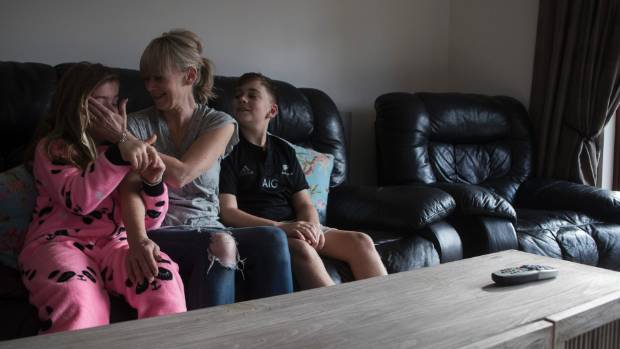 Kiri Reynolds at home with two of her three children  Artesia, 8, and Kiarn Collins, 10.