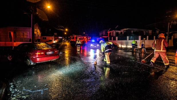 Fire crews sweep away debris after a crash in New Plymouth on Monday