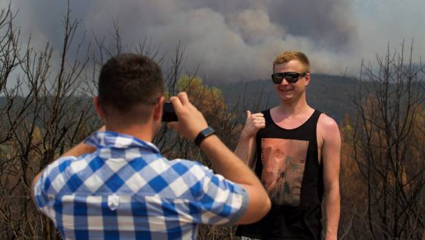 A tourist gives a thumbs-up as he poses for his friend's picture with a forest fire in the background at Lustica ...