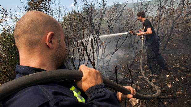 Firefighters try to extinguish a forest fire at Lustica peninsula near Tivat, Montenegro.