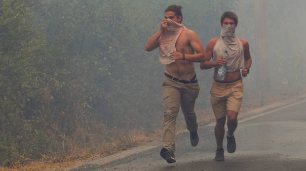 Tourists run through smoke during a forest fire at Lustica peninsula near Tivat, Montenegro.