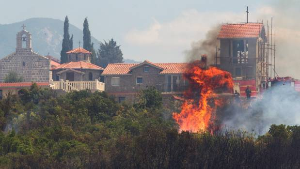 Firefighters try to extinguish a forest fire next to a monastery at Lustica peninsula near Tivat, Montenegro.