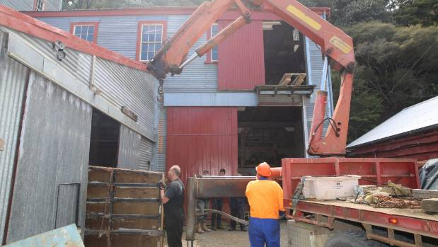 An old Wilfley shaker table is removed from the main building.