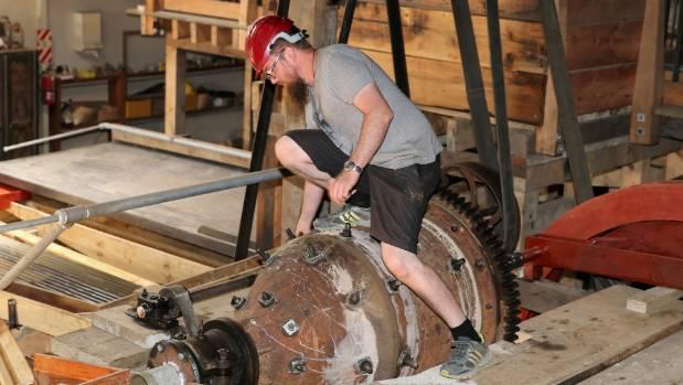 Historian Tom Barker tightens bolts on the ball mill.