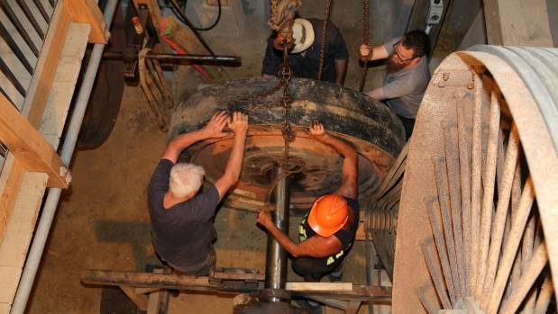 Volunteers install the flywheel and main stamper battery camshaft.