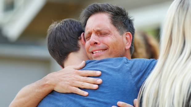 Don Damond hugs a neighbor after reading a statement about his fiance, Justine Damond who was fatally shot by ...
