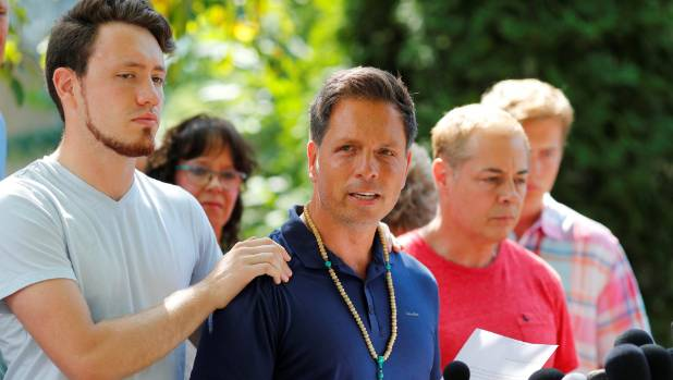 Don Damond is comforted by his son Zach Damond as he speaks to the media about his fiance Justine Damond who was