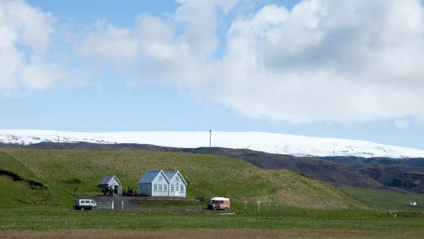 A small farmhouse stands below the Myrdalsjokull glacier that covers the Katla volcano in Evindarholar, Iceland.