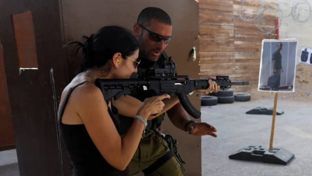 "An Israeli instructor guides a tourist as she fires a rifle during a two hour ""boot camp"" experience."