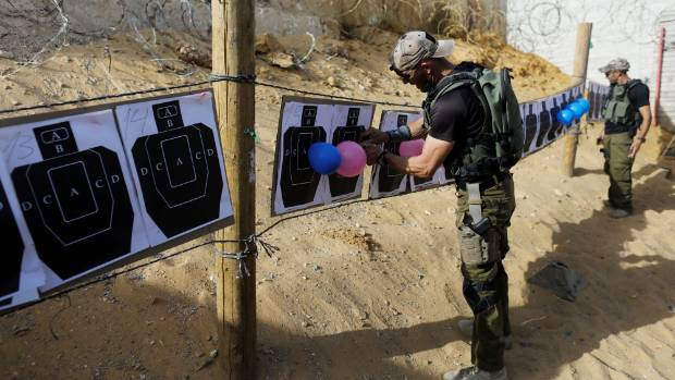 An Israeli instructor hangs up balloons on shooting targets.
