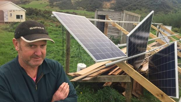 Lifestyle block owner Adrian Mourie with the damaged solar panel array on his property near Manakau, north of Otaki. ...
