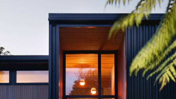 The glow from the entrance at dusk; the house is clad in a mixture of cedar boards and Colorsteel to keep costs down but ...
