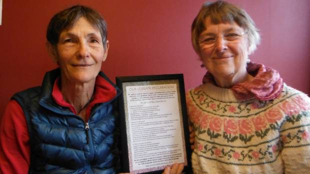 Katerina Seligman and Joanna Santa Barbara with a copy of Our Climate Declaration.