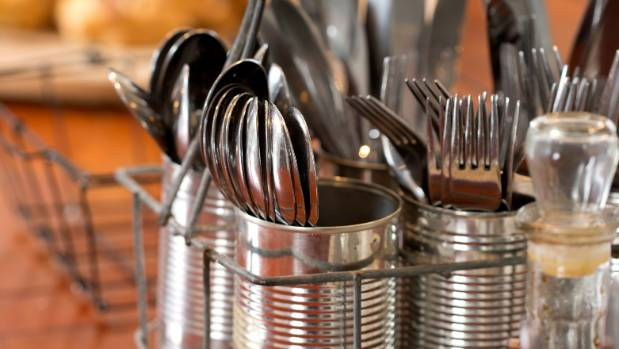 An old milk bottle carrier filled with recycled cans makes a perfect cutlery caddy.