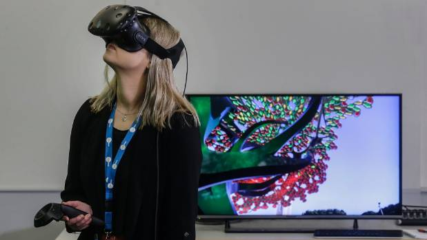 Reporter Ruby Macandrew trying out the virtual reality version of the war memorial design.