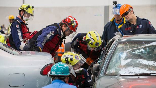 A New South Wales Firefighting teams puts jams a hydraulic tool in a car door as assessors watch on.