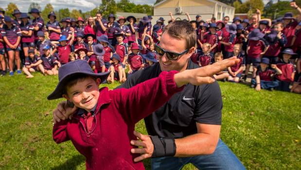 Tom Walsh giving Fergus Giles, 8, a hand with his technique at the  Pleasant Point Primary School after returning from ...