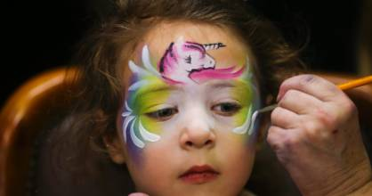 Mia Tutaki, 5, has her face painted with a unicorn by Jeanette Poulson from Feral Face Painting and Body Art.