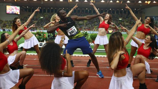 Usain Bolt is surrounded by cheerleaders as he performs his trademark archer pose after winning the 100m at the Monaco ...