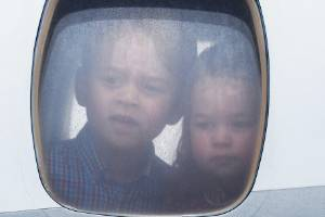 Princess Charlotte of Cambridge and Prince George of Cambridge look out of the window of the plane as they arrive at ...