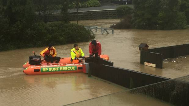 Rescue workers evacuate residents in Heathcote, Christchurch by boat.