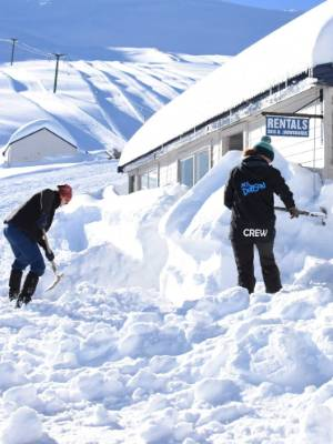 Staff clear snow from the base building at Mt Dobson on Sunday.
