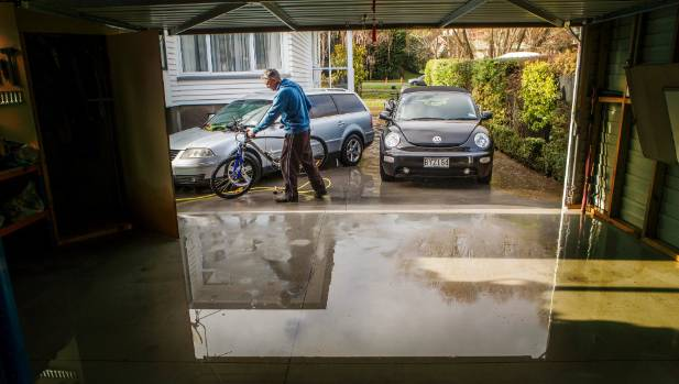 Chris Benn cleans bikes after flooding at his Eastern Terrace home. The two cars were flooded.