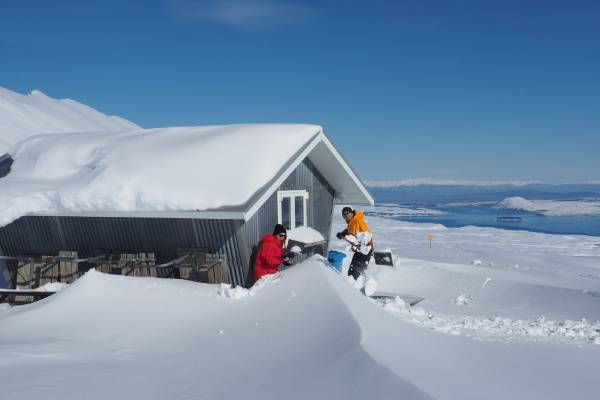 "Sophie Reider and Jan Zumbrunnen clear snow from around the ""Von Brown Hut"" at Roundhill Ski Field. Lake Tekapo is ..."